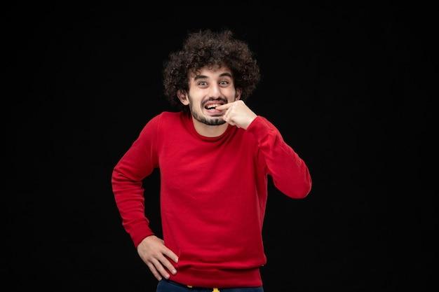Vorderansicht des jungen mannes im roten hemd aufgeregt auf schwarzer wand
