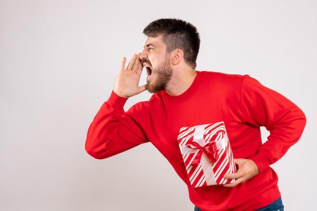 Vorderansicht des jungen mannes im roten hemd, das weihnachtsgeschenk hält, das laut auf weiße wand anruft Kostenlose Fotos