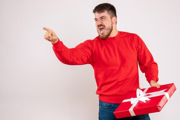 Vorderansicht des jungen mannes im roten hemd, das weihnachtsgeschenk hält und mit jemandem auf weißer wand argumentiert