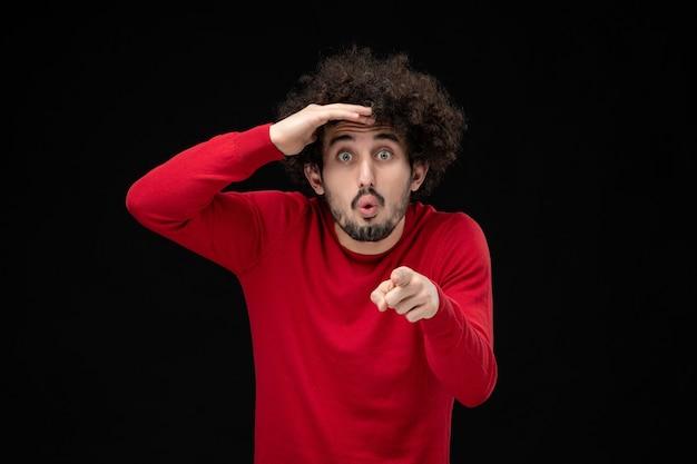 Vorderansicht des jungen mannes im roten hemd, der auf die schwarze wand in die ferne schaut