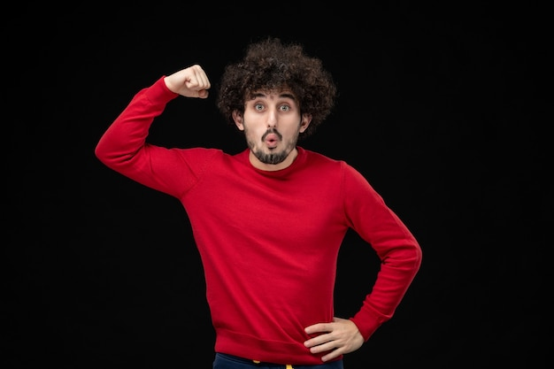 Vorderansicht des jungen mannes im roten hemd, der sich an der schwarzen wand biegt