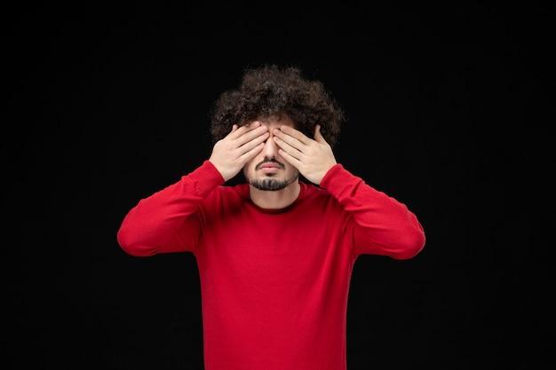 Vorderansicht des jungen mannes im roten pullover an der schwarzen wand