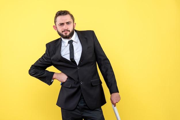 Vorderansicht des jungen mannes im schwarzen anzug, der ernst mit einer hand auf der seite und anderen hält, die leere papierblätter auf gelb halten