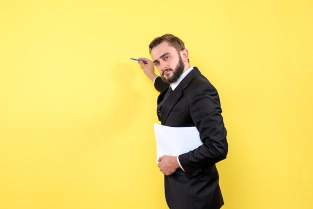 Vorderansicht des jungen mannes im schwarzen anzug, der mit einem stift auf die gelbe wand zeigt