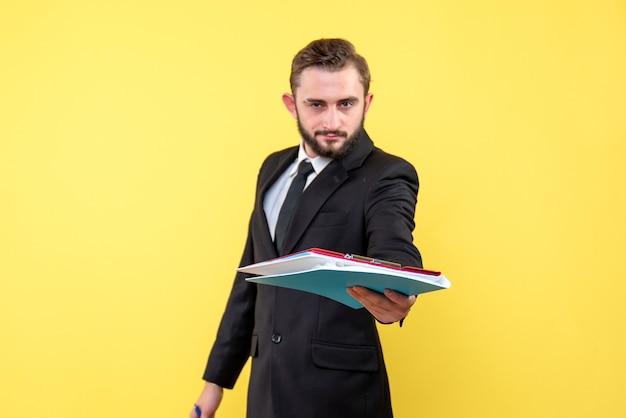 Vorderansicht des jungen mannes im schwarzen anzug, der ordner und zwischenablage mit dokumenten auf gelb übergibt
