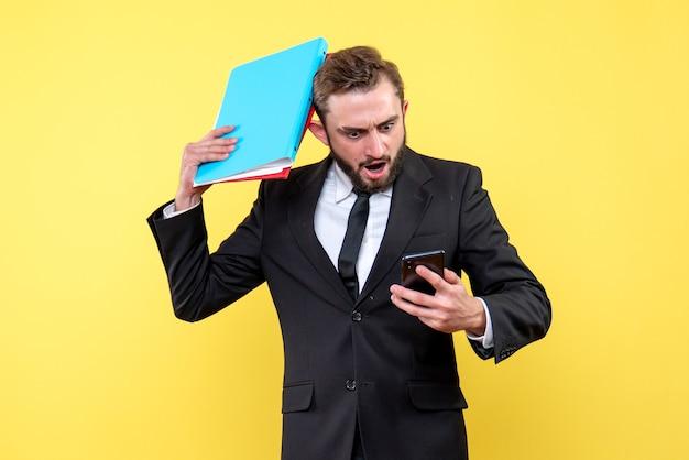 Vorderansicht des jungen mannes im schwarzen anzug schockierend, der ein mobiltelefon betrachtet und kopf mit ordnern auf gelb berührt