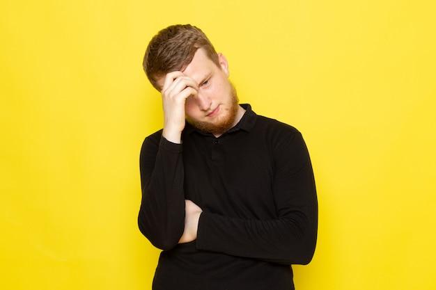 Vorderansicht des jungen mannes im schwarzen hemd, das aufwirft und denkt