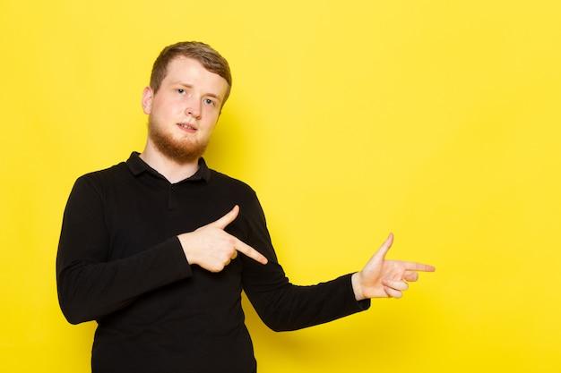 Vorderansicht des jungen mannes im schwarzen hemd, das aufwirft
