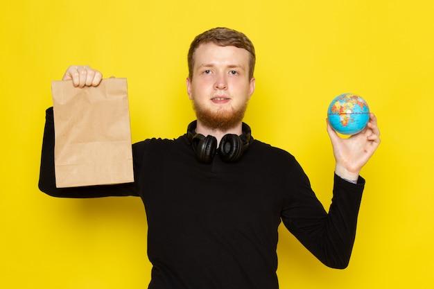 Vorderansicht des jungen mannes im schwarzen hemd, das lebensmittelpaket und kleinen globus hält