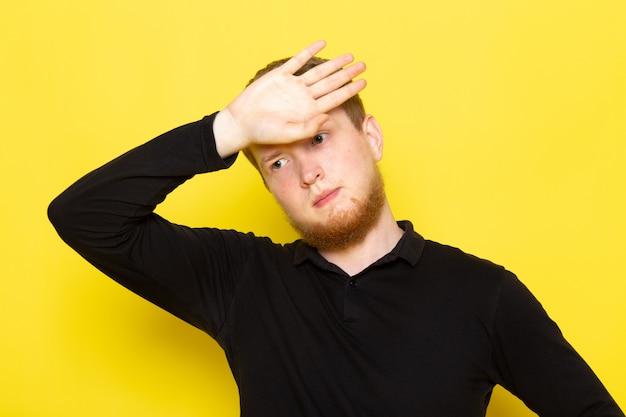 Vorderansicht des jungen mannes im schwarzen hemd, das mit dem müden ausdruck aufwirft