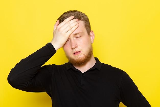 Vorderansicht des jungen mannes im schwarzen hemd, das mit enttäuschtem ausdruck aufwirft