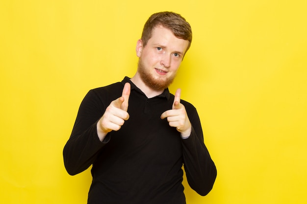 Vorderansicht des jungen mannes im schwarzen hemd, das mit guter laune aufwirft