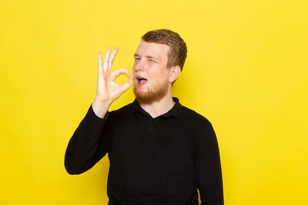 Vorderansicht des jungen mannes im schwarzen hemd, das mit lustigem ausdruck aufwirft