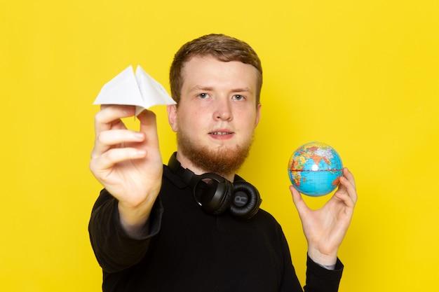 Vorderansicht des jungen mannes im schwarzen hemd, das papierflugzeug und kleinen globus hält