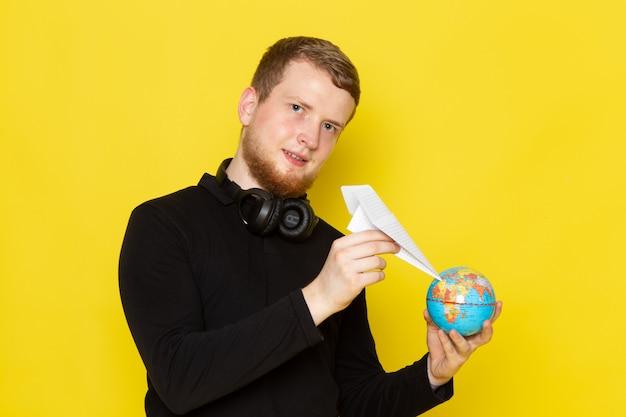 Vorderansicht des jungen mannes im schwarzen hemd, das papierflugzeug und kleinen globus mit lächeln hält
