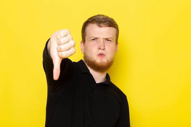 Vorderansicht des jungen mannes im schwarzen hemd, das unähnliches zeichen aufwirft und zeigt