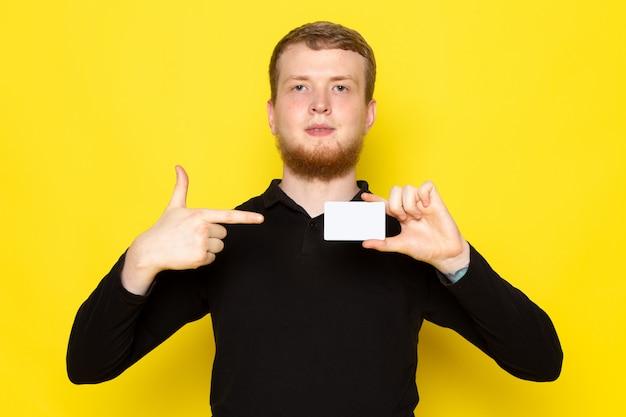 Vorderansicht des jungen mannes im schwarzen hemd, das weiße karte auf der gelben oberfläche hält
