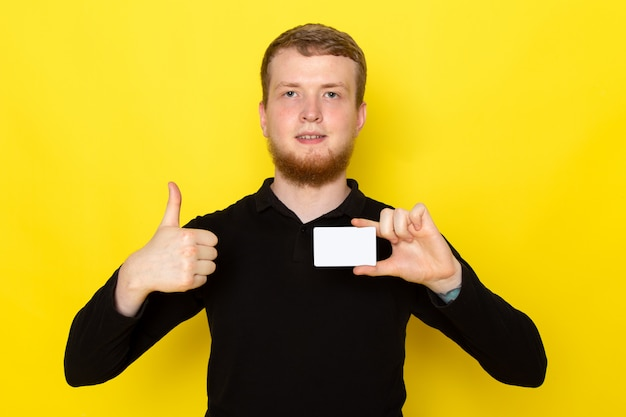 Vorderansicht des jungen mannes im schwarzen hemd, das weiße karte hält