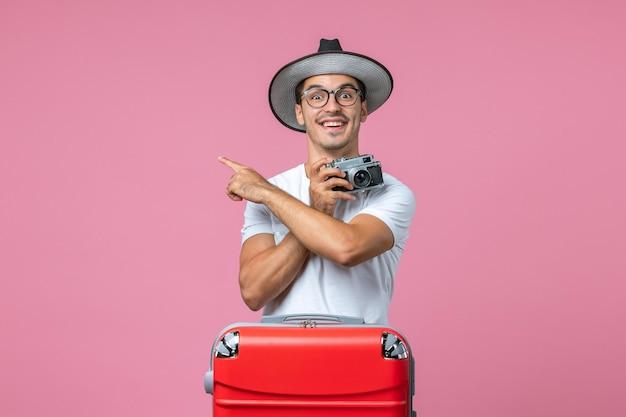 Vorderansicht des jungen mannes im sommerurlaub, der fotos mit der kamera an der rosa wand macht