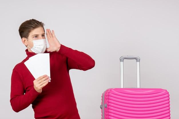 Vorderansicht des jungen mannes in der maske, die flugtickets auf weißer wand hält