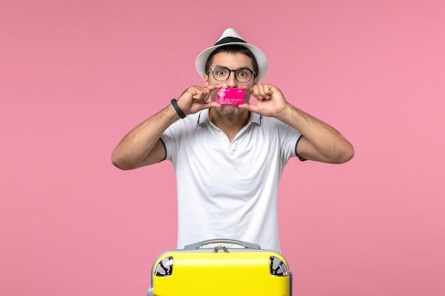 Vorderansicht des jungen mannes mit bankkarte im sommerurlaub an der rosa wand