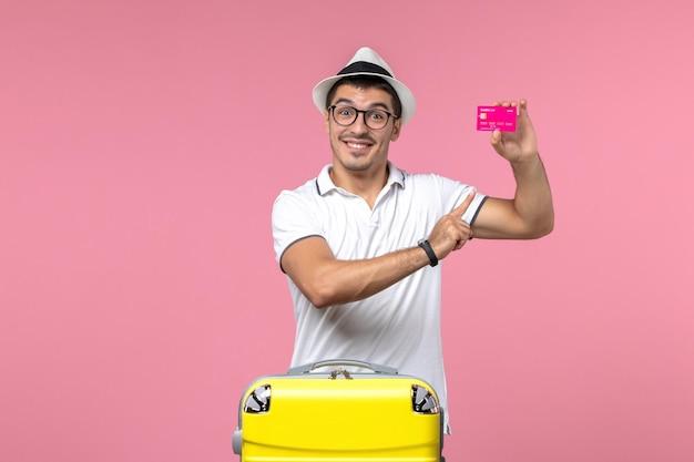 Vorderansicht des jungen mannes mit bankkarte im sommerurlaub an hellrosa wand