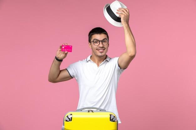 Vorderansicht des jungen mannes mit bankkarte im urlaub an der rosa wand pink