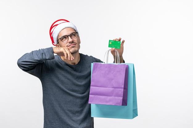 Vorderansicht des jungen mannes mit bankkarte und paketen auf weißer wand