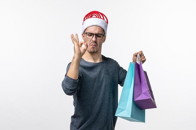 Vorderansicht des jungen mannes mit geschenken nach dem einkaufen an der weißen wand