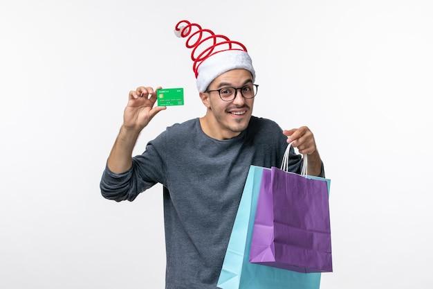Vorderansicht des jungen mannes mit geschenken und bankkarte auf weißer wand