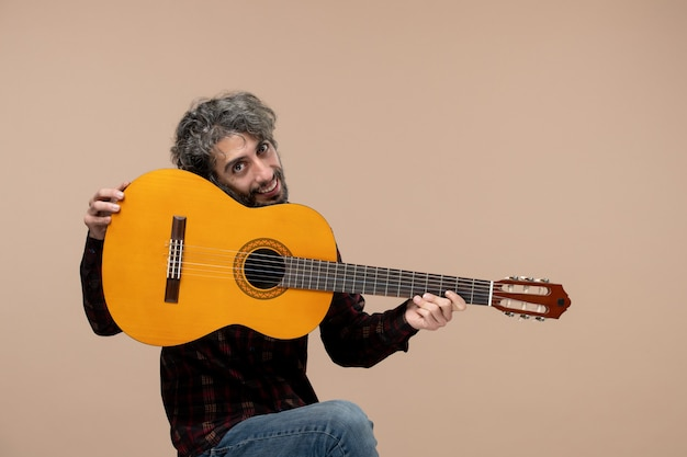 Vorderansicht des jungen mannes mit gitarre an der rosa wand