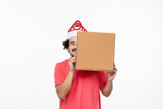 Vorderansicht des jungen mannes mit lieferbox an weißer wand