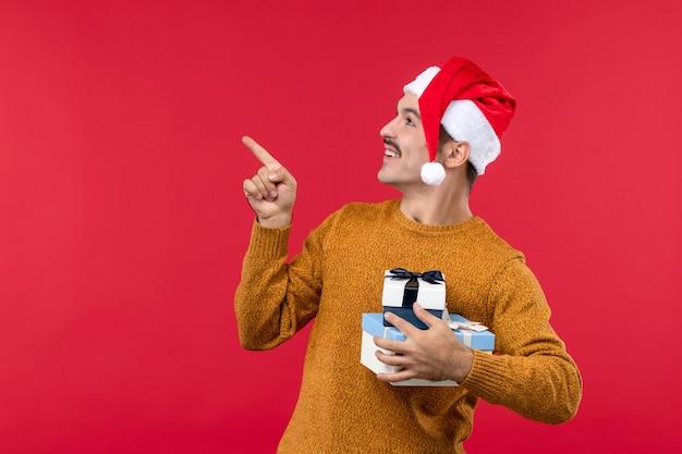 Vorderansicht des jungen mannes mit neujahrsgeschenken an der roten wand