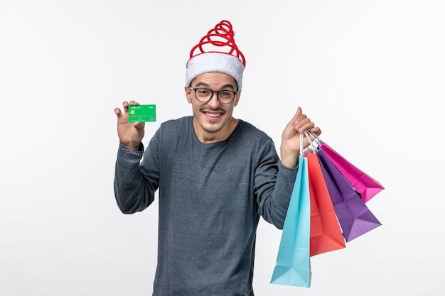 Vorderansicht des jungen mannes mit paketen und bankkarte auf weißer wand