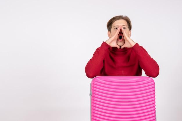 Vorderansicht des jungen mannes mit rosa tasche, die weiße wand anruft