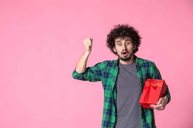 Vorderansicht des jungen mannes mit rotem paket auf hellrosa wand