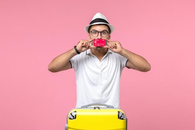 Vorderansicht des jungen mannes mit roter bankkarte im sommerurlaub an der rosa wand