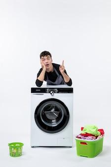 Vorderansicht des jungen mannes mit schmutziger kleidung und waschmaschine auf weißer wand