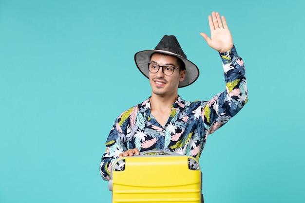 Vorderansicht des jungen mannes mit seiner gelben tasche, die sich auf die reise vorbereitet, die jemanden an der blauen wand begrüßt