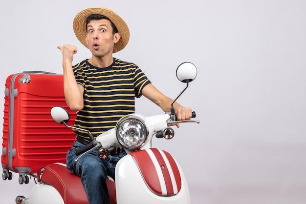 Vorderansicht des jungen mannes mit strohhut auf moped, der auf etwas mit großem interesse zeigt