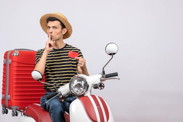 Vorderansicht des jungen mannes mit strohhut auf moped hält kreditkarte, die shh zeichen macht