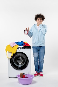 Vorderansicht des jungen mannes mit waschmaschine, die uhren an der weißen wand hält