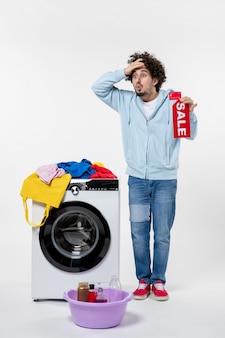 Vorderansicht des jungen mannes mit waschmaschine mit rotem verkaufsbanner auf weißer wand