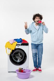 Vorderansicht des jungen mannes mit waschmaschine mit roter bankkarte auf weißer wand