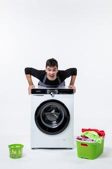 Vorderansicht des jungen mannes mit waschmaschine und schmutziger kleidung auf weißer wand