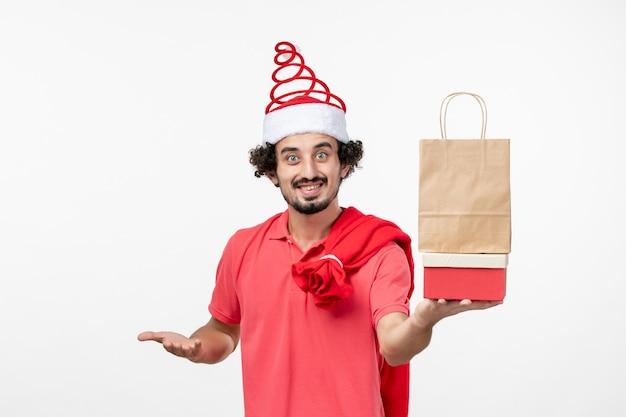 Vorderansicht des jungen mannes mit weihnachtsgeschenken an der weißen wand