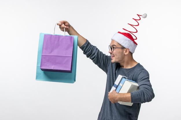 Vorderansicht des jungen mannes mit weihnachtsgeschenken auf weißer wand