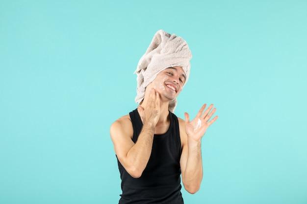 Vorderansicht des jungen mannes nach dem duschen, der sein gesicht an der blauen wand eincremet