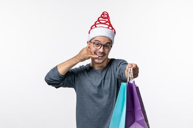 Vorderansicht des jungen mannes nach dem weihnachtseinkauf an der weißen wand