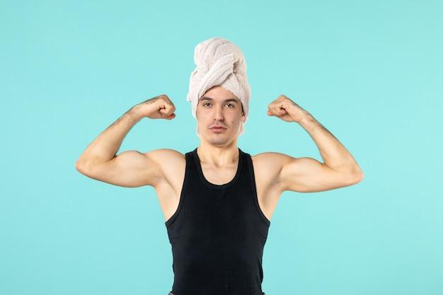 Vorderansicht des jungen mannes nach der dusche, der sich an der blauen wand biegt